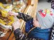 dziecko wyciągające rękę po piernik z wiklinowego koszyczka